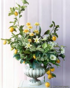 The natural lines of lemon boughs create balanced curves in this arrangement of jonquils, amaryllis, anemones, lilacs, hellebore, and speckled foliage