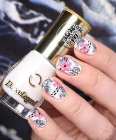 Gray and pink flower nail - White, gray and pink floral nail art design. With a matte background of white, draw gray silhouettes of flowers and leaves on your nails topped with a bigger pink hibiscus flowers on top followed by thin black nail polish dotted lines across the nails.