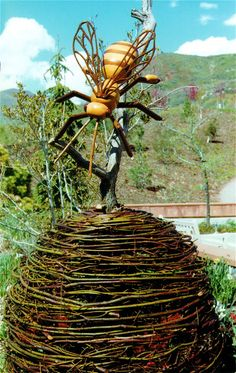 A bee sculpture with a woven nest mounted on a tree - fab idea