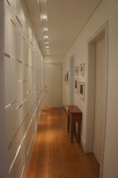 No corredor de acesso às suítes de um apartamento, o arquiteto Luis Navarro idealizou um roupeiro de um lado e do outro pendurou quadros. Repare que painéis desconexos em alto e baixo relevo, destacados pela iluminação, dão movimento e textura ao ambiente. Como os puxadores são embutidos.