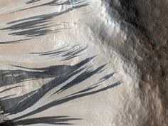Dark and light streaks crawl up a ridge in this picture of the Acheron Fossae region. Scientists debate over how the different-colored streaks formed, but they agree that the darker streaks are younger that turn into the lighter streaks over time.