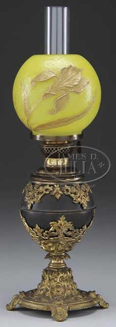 lighting, America, Brass plated metal junior banquet lamp with fancy stem and foot; drop in font with P. and A. Victor burner; orange-textured ball shade in yellow glass with embossed iris patten highlighted in gold CIRCA 1850-1900