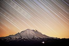 This image captures almost 6 hours of climbing parties on Rainier going for the summit under starry skies. Wind shifts during the night would cause bands of smoke from fires 100 miles away on Mt Hood to pass over Rainier. This intermittent low-level haze caused the red glow seen in the sky and a Rainier that looks like it was almost painted on. Lights from Sunrise can be seen in the lower right of the frame. (© Chris Morin)