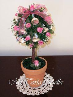 Arbolito con chocolates kisses plateados y flores rosadas.