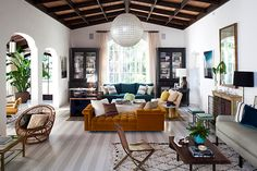 "Nate Berkus Associates sought to create a ""light, livable and airy"" atmosphere for the owner of this Los Angeles home using a diverse approach to materiality — the room includes iron, brass, rattan and greenery — plus jewel-toned upholstery and painted wood floors."