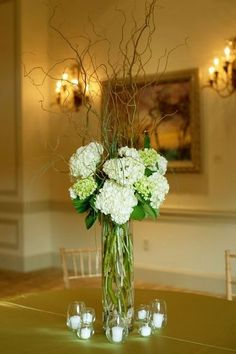 willow branches for flower arrangements for weddings | Hydrangeas in tall case with curly willow branches
