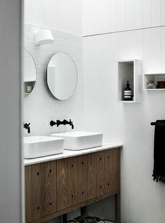 okragłe lustra,czarne baterie retro,drewniane rustykalne szafki pod prostokatnymi umywalkami,drewniane biale panele na ścianie i biało-czarna marokańska  terakota w łazience