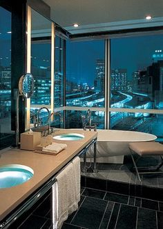 A bath with glass sinks looks out over the lights of Tokyo.