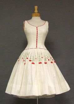 WOW! What a dress! Ivory cotton eyelet with bright red piping and buttons on the fitted sleeveless bodice. Dress has a full skirt with red & green floral embroidery and an attached crinoline