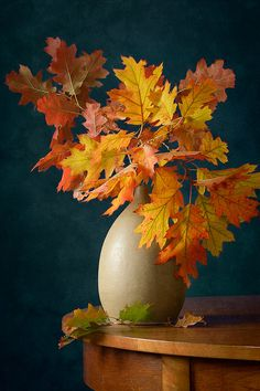 http://nikolay-panov.artistwebsites.com/products/fall-colors-nikolay-panov-art-print.html  • Floral still life with bouquet of bright yellow and red fall leaves in brown vase on wooden table in autumn