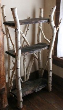 Rustic Shelves: Birch branches and dark wood slabs.