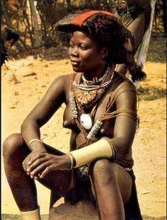 """Ovimbundo woman . Angola .  Os Ovimbundu são uma etnia bantu de Angola.  Os seus subgrupos mais importantes são os Mbalundu (""""Bailundos""""), os Wambo (Huambo), os Bieno, os Sele, os Ndulu, os Sambo e os Kakonda (Caconda).  História Descendentes de populações bantu que chegaram à região no início do 2º milénio, os Ovimbundu ocupam hoje o planalto central de Angola e a faixa costeira adjacente, uma região que compreende as províncias do Huambo, Bié e Benguela."""