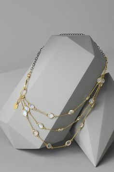 jewelry draped on gemstone shaped cardboard boxes painted an elegant pale grey.