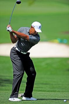 Tiger Woods hits on the practice range at Augusta National Golf Club on Sunday, April 1, 2012, in Augusta, Ga