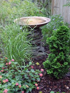 Copper Bird Bath... I love the stones and the way the fountain is partially concealed by the flowers and greenery.
