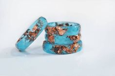 This blue resin ring contains metallic copper flakes suspended in hand pigmented blue resin. You can wear only one or you can stack two or three rings on a finger. This listing is for ONE blue resin ring with copper flakes.  Handmade by me from scratch, each one of my pieces is hand pigmented, and poured into a silicone mold. After I remove it from the mold I hand sand it for you to have a smooth and comfortable piece to wear. The ring is matte on both sides.  Please keep in mind that each…