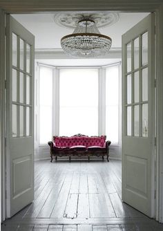House in London features the perfect mix of Victorian & modern furnishings. This space has a crystal chandelier hanging above wood floors & a pink gilded, button-tufted sofa.