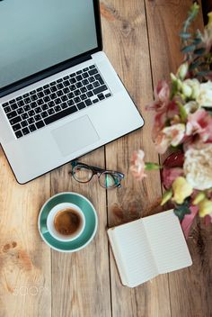 Delicious morning coffee at the workplace. Laptop and beautiful flower bouquet on the wooden background