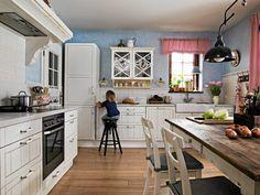 Stylizowane meble, dużo drewna, bieli i błękitu to dobra baza do przytulnej kuchni.