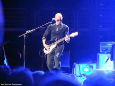 """Simon, playing his twelve-string during """"Love, Reign O'er Me."""""""