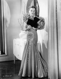 """This gown was designed by Bernard Newman and is worn by a fashion model for the film 'Roberta', 1935."""