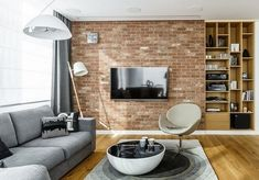 living trends 2016 gray sofa red brick wall flat screen TV round coffee table carpet
