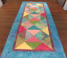 Sun Shinny Day Multi Colored Batik Table Runner 18 1/4 x 41 3/4 inches This table runner just reminds me of a sun shinny day. All the bright batik colors bring the beautiful colors of the outdoors into your home. This table runner is a beautiful colorful collection of batiks that
