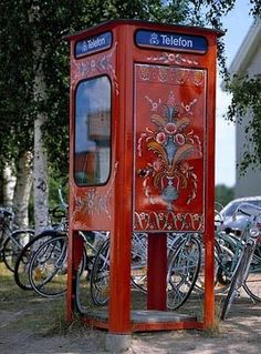 Swedish red (falun red) telephone booth with traditional kurbits design.