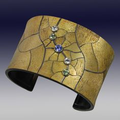 WolfganVaatz ~ Cuff in 18k gold fused on sterling silver, oxidized with 5 mm tanzanite, 4 mm white beryls, and 4 mm green tourmalines.