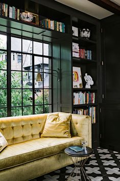 This very dark green and nearly black library looks beautiful, especially with the garden view and in comination with the velvet couch in a much brighter shade of green and nearly yellow. And of course, you have to have a look at the patterned floor. Brilliant!