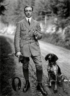 This is a man who is wearing a Norfolk Jacket in the typically setting of him getting ready to hunt. The jacket has the same details with the pleats and belt wrapping around the waist.