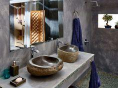 Recupera la esencia de lo natural en el baño con un lavabo de piedra sin pulir sobre encimera de madera: la belleza de lo imperfecto se pone en valor esta temporada.