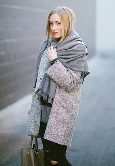 Oversized scarf draped over a grey coat and distressed jeans