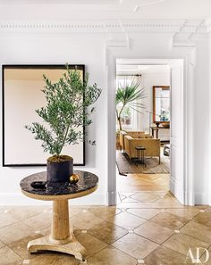 In Nate Berkus and Jeremiah Brent's New York apartment, a Matt Connors painting is mounted behind a 19th-century French pedestal table in the entrance hall, which has a French limestone floor.