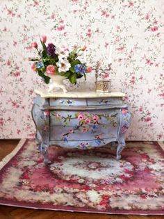 Lovely one-of-a-kind floral arrangement. Laura Crain's hand-painted blue chest beautifully compliments the floral display. Good Sam Showcase of Miniatures