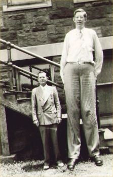 Robert Wadlow, tallest man who ever lived, with his father.  Robert Wadlow was 8'11'' and his father was 5'11''.  This photo is interesting because there is an optical illusion going. Because his father is standing lower than Robert, it makes Robert look even taller.  He usually came up to slightly above Robert's waist.
