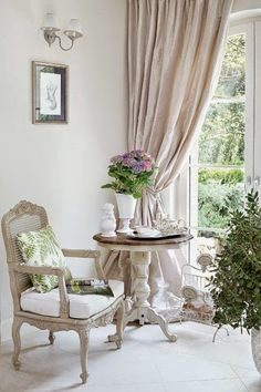 Elegant corner with an antique French chair and fresh flowers on a round table against heavy silk curtains. Perfectly finished.