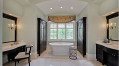 Traditional bathroom with white tub, dark wood sinks and cabinetry, and single classic chair