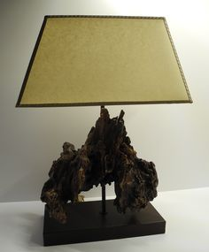 Table lamp. Wooden base covered in dark brown calfskin. Natural sculpture of wood harvested from a mountain stream. Hat parchment finished in antique trimmings.