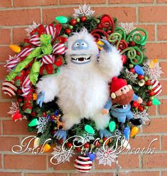 **READY TO SHIP** This PERFECT Christmas wreath is a Collectors item all by itself! This ONE OF A KIND Christmas Wreath features Vintage Christmas Memories you wont find anywhere else! Front and center is a Discontinued 16 Posable plush Rudolphs Ultimate Abominable Snow Monster, accompanied by an 8 plush Yukon Cornelius, 3 inch PVC Rudolph figurine, peppermint ball ornaments, C9 ceramic vintage style LED cool-touch string lights, green red glitter ball garland, and snow snow snow flakes…