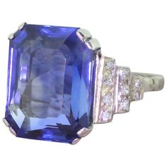 Art Deco 10.82 Carat Emerald Cut Natural Sapphire Gold Platinum Ring. An immense sapphire. This glorious ring features a rich, bright blue emerald cut natural sapphire. Set in a stunning Art Deco mount featuring 18 (nine either side) eight cuts diamonds in a geometric, step down design. Rare, striking and undeniably beautiful. c 1935