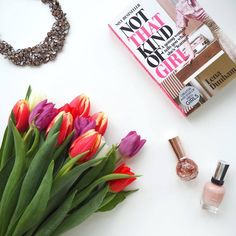 Flat lay fashion blogger instagram style styling photography layout arrangement. Flowers pink colour not that kind of girl by lena dunham nail varnish zar neckland. kitty blogger clothes and stuff. instablogger tulips inspiration flatlay
