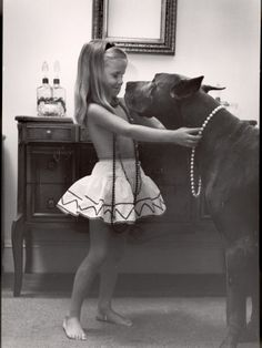 little girl puts her pearls on her great dane
