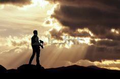 Hombre en lo alto de una montaña entrena a su halcón en una espectacular puesta de sol