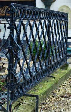 A wrought iron fence takes a utilitarian structure and turns it ...