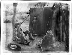 """Three Havasupai Indians, Waluthama, his father and daughter, in front of their """"Hawa"""" or dwelling, ca.1899"""