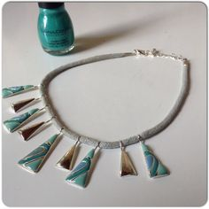 "TEAL & SILVER NECKLACE Hand made teal & silver necklace on pale blue rope at offers a beach like look!  The silver pendants alternate with the teal & cream painted pieces. Lobster claw clasp in silver with 9"" drop & a bit of room for adjustment. Jewelry Necklaces"