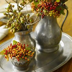 Branch Out - The patina of tarnished pewter contrasts with fall foliage in this rustic-meets-refined grouping. Tuck acorns, viburnum, and crab apple cuttings (find at a florist or gather from the yard) in a trio of staggered-size containers, corralling on a tray. Total time: eight minutes.