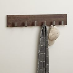 This smart wall mounted coat rack hangs on clean lines and contrasting materials for a contemporary look with plenty of function. Angular, zinc-finished iron coat hooks line up along a sustainable mango wood plank with a weathered walnut brown finish.