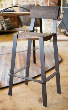 This rustic counter height stool has a great minimalist design that matches any contemporary environment. Order this metal and reclaimed wood bar stool today!